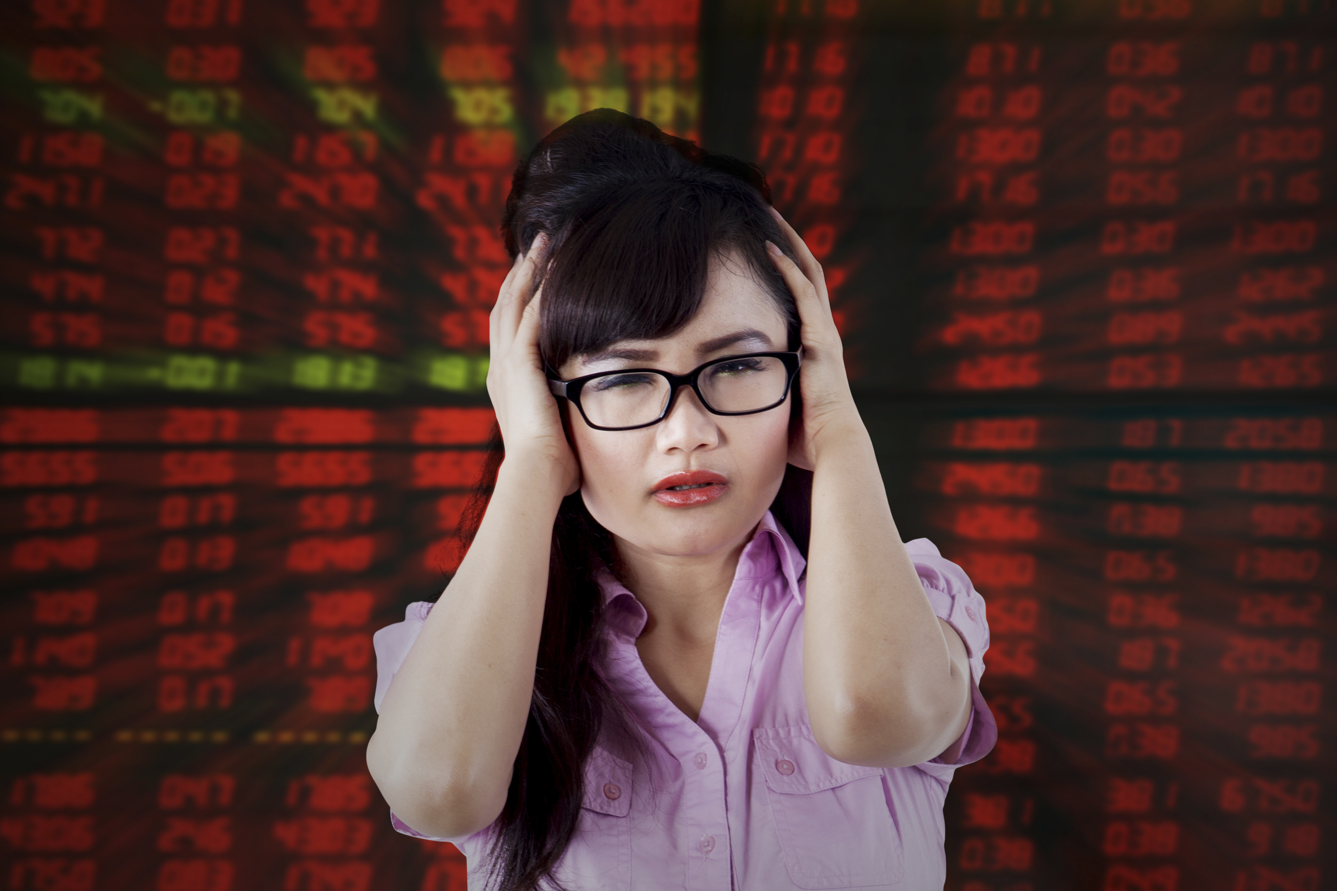 Image of young businesswoman looks stressful with red stock exchange background